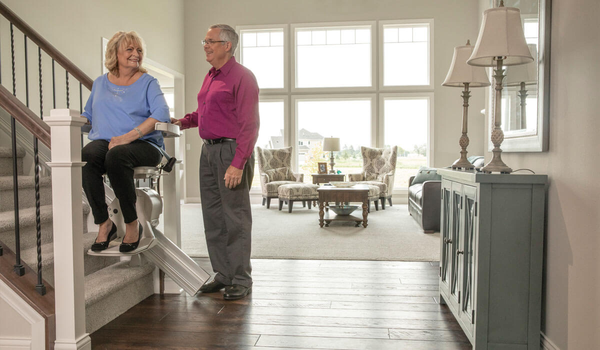 Woman on stair lift with man standing next to herWoman on stair lift with man standing next to her